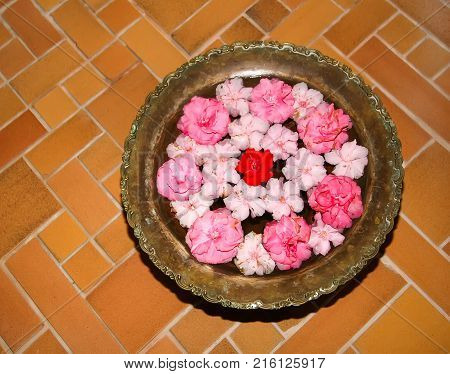 Buds of flowers floating in a large plate standing on the floor