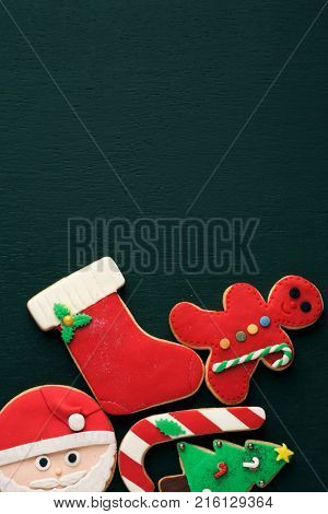 some homemade cookies with different shapes, such as a candy cane, a gingerbread man, a christmas tree, a christmas stocking or the face of santa on a dark green background with a blank space on top