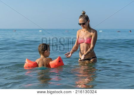 Young mother in black sunglasses and smiling baby boy son playing in the sea in the day time. Positive human emotions feelings joy. Splash. Spring and summer holidays.