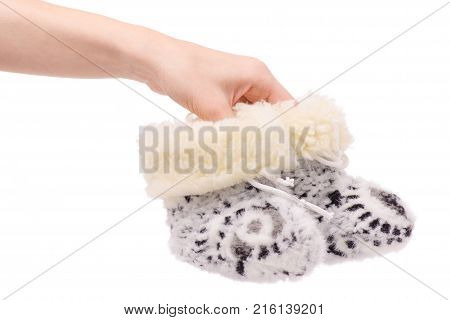 baby's bootees fur warming in female hands on a white background isolation