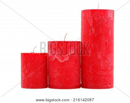 Three different sized red wax candles with a wick, isolated on a white background, stand, all different in height, the concept of holidays, new year, St. Valentine's Day