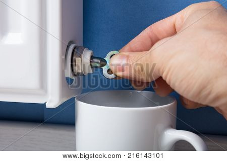 Close-up Of Person's Hand Turning Radiator Bleed Valve To Release Air With Cup At Home