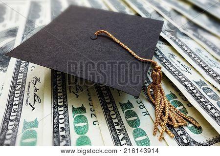 Mini graduation mortar board cap on money -- education cost or scholarship concept