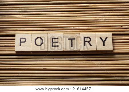 Word POETRY written on wooden cubes. Wooden abc.