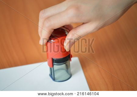 Female hand hold rubber stamps over blank paper corner at office table, closeup detail shoot