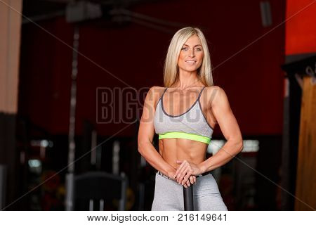 Close-up of a girl, blonde in a gym training, posing, standing with a hammer, looking away. The concept of a healthy lifestyle.