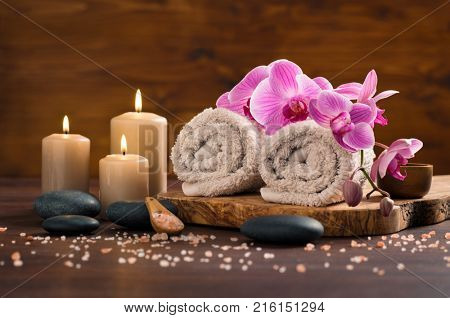 Spa setting with brown rolled towel, orchids and candles on wood. Relaxing spa concept with candles, towels and hot stones massage with himalayan salt. Beautiful composition for beauty treatment.