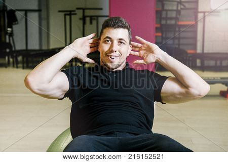 Man pumping the press. Portrait of an athlete. Lifting dumbbells. Physical exercises.Work of personal trainer. Portrait Of Personal Trainer In Sports Outfit In Fitness Center Gym Standing Strong.