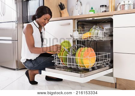 Smiling Young African Woman Arranging Plates In Dishwasher poster