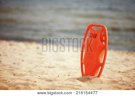 Beach life-saving. Lifeguard rescue equipment orange preserver tool red plastic buoyancy aid in the sand