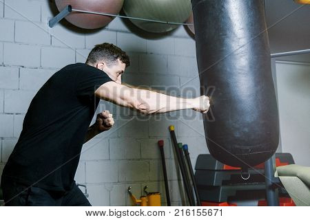 Personal boxing trainer. guy trains with boxing pear.  Work of personal trainer. Portrait Of Personal Trainer In Sports Outfit In Fitness Center Gym Standing Strong.