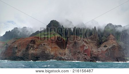 Panoramic of Beautiful Na Pali Coast with clouds covering the tops as seen from off shore.