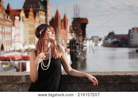 Flapper girl. Retro style fashion vintage woman from roaring 1920s outdoor on the street. Old town Gdansk Danzig in the background