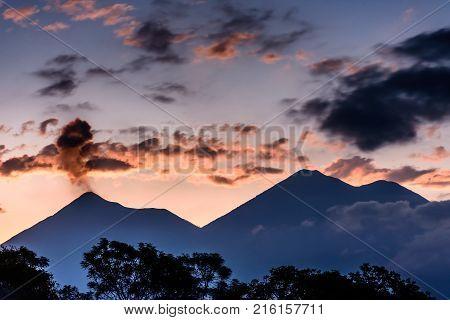 Puffs of smoke erupt from Fuego volcano next to Acatenango volcano near Antigua, Guatemala, Central America