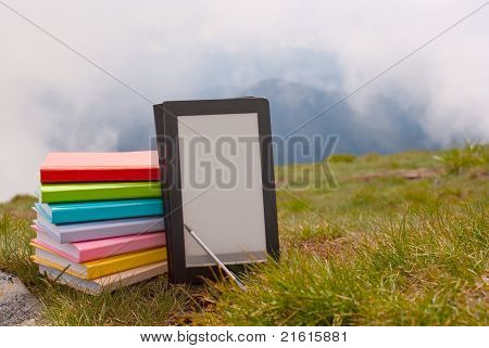 Stack Of Colorful Books And Electronic Book Reader On The Grass