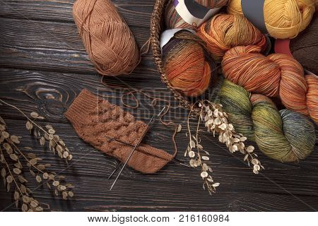 Autumn colors in woolen yarn. Handmade woolen socks with dry plants. Still life with knitting yarn and socks on wooden background