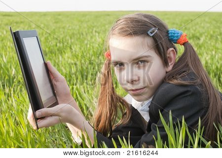 Teen Girl With Electronic Book Laying On Grass