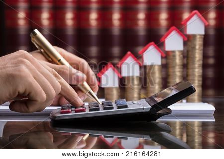 Person Calculating Invoice With Calculator In Front Of Stacked Coins And House Model