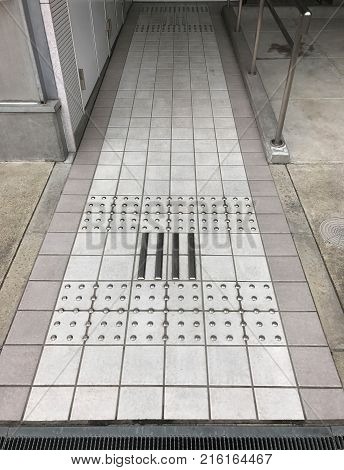 Tactile stainless steel walkway on ceramic tile for blind people