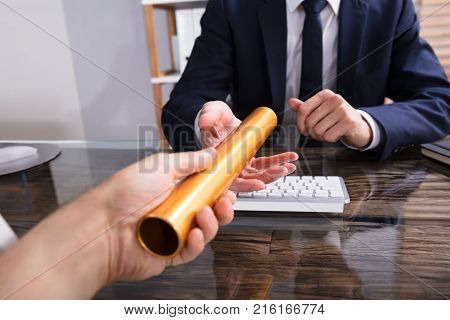 Close-up Of A Person's Hand Passing Golden Relay Baton To Businessperson