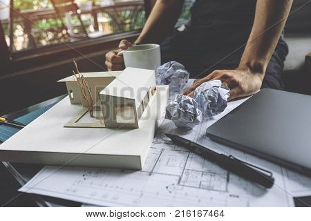 Closeup image of a stressed architects thinking and drawing shop drawing paper with architecture model and laptop on table with feeling fail