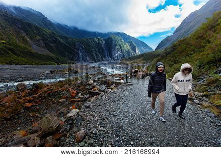 FRANZ JOSEF GLACIER NEW ZEALAND - SEP42015 : unidentified tourist trekking in franz josef glacier natural trail franz josef is most popular traveling destination in west coast of south island of new zealand