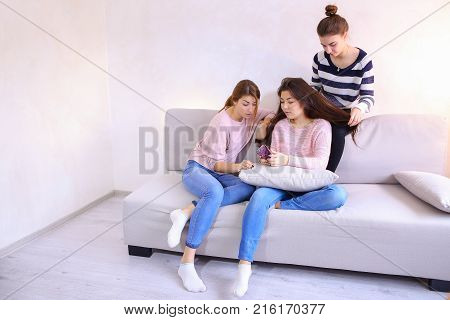 Lovely women spend time together and engaged in women's affairs. Two women help to get girlfriend to meet with guy, paint nails and lips, braid hair, chat and joke, sitting on soft gray sofa in bright room in evening.