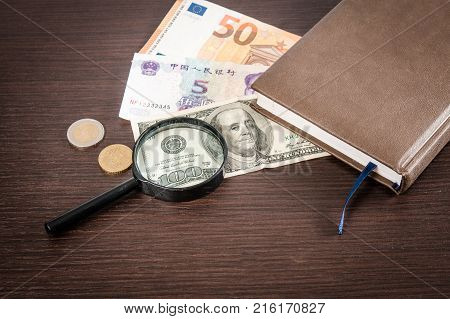 Banknotes and coins lying on notepad stickers with currency signs and Magnifier on wooden table. Accounting and taxes.