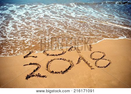 New Year 2018 is coming concept - inscription 2017 and 2018 on a beach sand the wave is covering digits 2017. New Year 2018 celebration on New Year`s Eve tropical island travel tour.