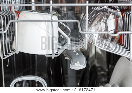 Open dishwasher with clean glass and dishes. Clean glasses after washing in the dishwasher.