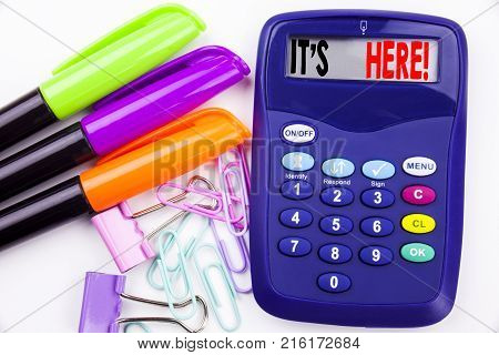 Writing Word It's Here Text In The Office With Surroundings Such As Marker, Pen Writing On Calculato