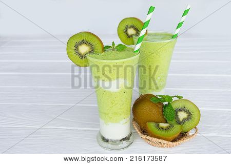 Kiwi smoothies and kiwi fruit for breakfast in the morning on a wooden floor.