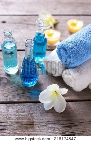 Bottles wih essential aroma oil candles and towels on wooden background. Selective focus. Vertical image.
