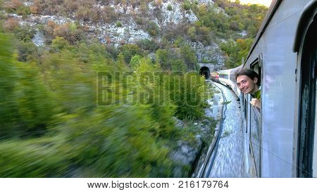A brave young girl leans out the window fast moving train approaching the tunnel. She laughs and happy journey