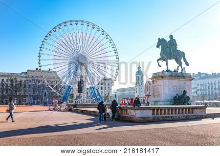 Lyon France - December 8 2016: Bellecour square with the equestrian monument of King Louis XIV and the big Ferris wheel in the background