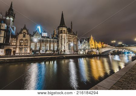 Ghent, Belgium - January, 3th, 2017. Saint Michael's bridge view with houses and Clock tower on Graslei embankment reflected in canal by evening lights. Gent night illumination. Long exposure shot.