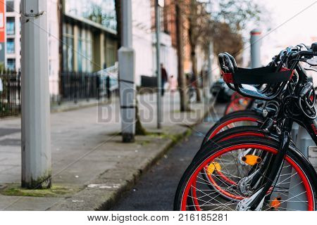 Cork, Ireland - November 12, 2017: Bicycles in parking rack in the city of Cork. Focus on foreground wheels