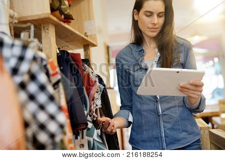 Shop owner checking stocks with digital tablet