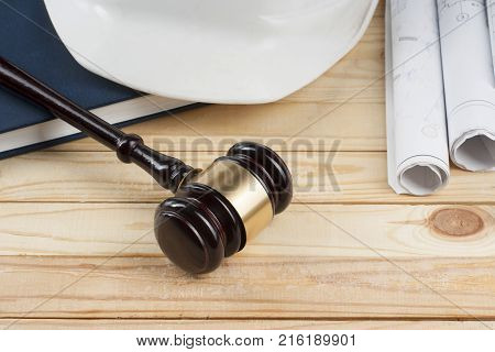 White helmet, drawings and judges gavel on wooden background. Law and construction concept