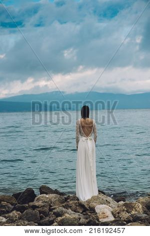 Beautiful Bride standing by the Sea. Destination wedding concept. Wedding on exotic island. Bride in white wedding dress watching sea.