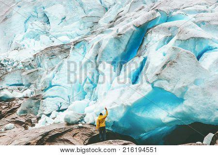 Traveler Man enjoying Nigardsbreen glacier view Travel Lifestyle getaway concept adventure extreme vacations outdoor nature in Norway
