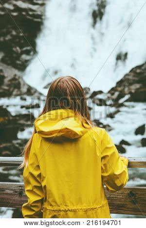 Tourist woman sightseeing waterfall outdoor Travel Lifestyle wanderlust concept adventure vacations in Norway wearing yellow raincoat clothing poster