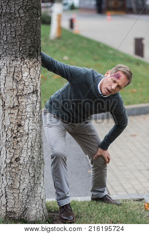 injured middle aged man with wound on head leaning on tree on the street