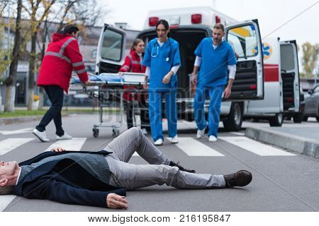 doctors running to wounded middle aged man lying on a street