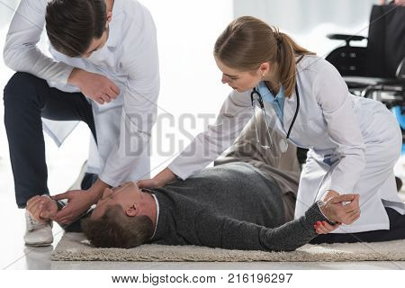 doctors checking pulse of unconscious mature man