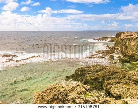Panorama of cliffs and wild coastal stretch of Grande-Terre in Guadeloupe island, French Caribbean and French Antilles. Summer season.