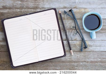 Blank paper notebookglassespencil and cup of coffee on brown wooden table background. Top view with copy space (selective focus). Office desk table concept.
