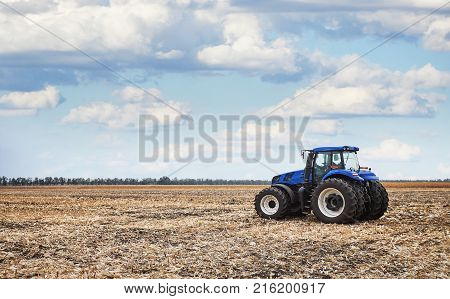 Tractor working on the farm, a modern agricultural transport, fertile land, tractor on cloudy sky background, cultivation of land, agricultural machine