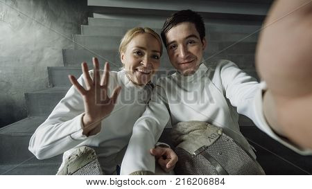 POV of Two young fencers man and woman having online video call with trainer using smartphone camera after fencing competition indoors