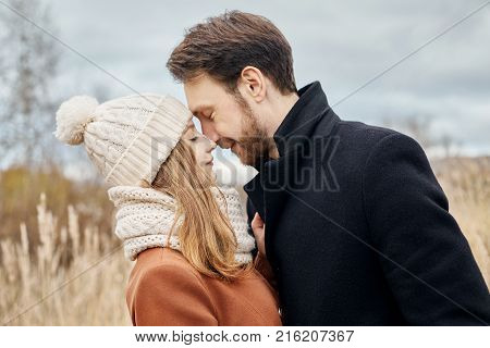Loving Couple Walking In Park In Autumn Hugs And Kisses. Autumn Walk Men And Women In The Woods On T